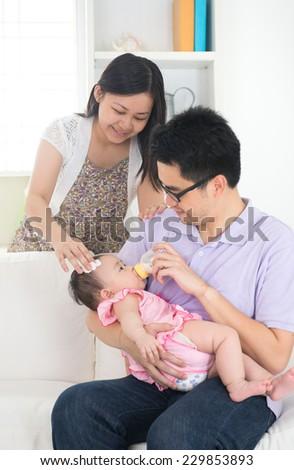 asian parents bottle feeding their baby - stock photo