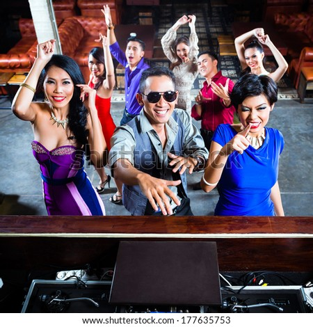 Asian party people men and women partying on the dance floor in fancy night club - stock photo
