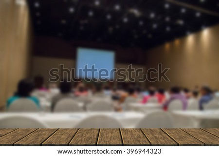 Asian people participate in seminar in the auditorium (blur background with wood table top for display or montage your product)l - stock photo