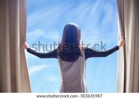 Asian portrait beautiful woman opening curtains and cloud blue sky background - stock photo