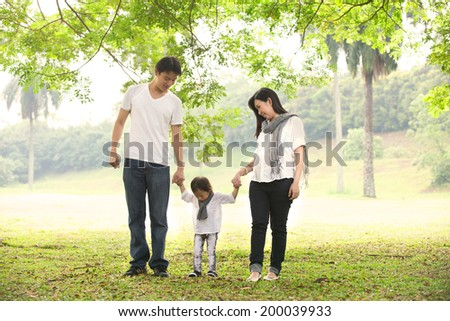 asian pregnant mother with husband family outdoor photo  - stock photo