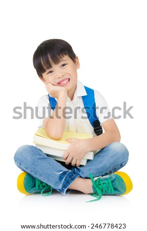 Asian preschool boy with schoolbag and books sitting on the floor - stock photo