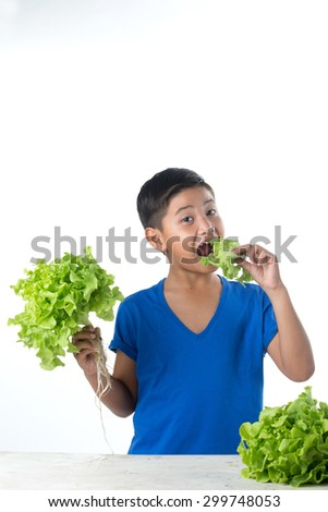 Asian pretty boy holding vegetables salad and eat - stock photo