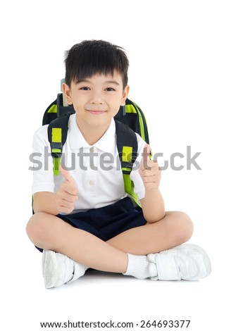 Asian primary school student sitting on the floor with his thumbs up - stock photo