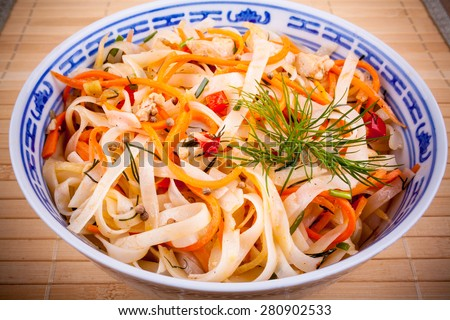 Asian rice noodle salad with chicken meat and carrots - stock photo