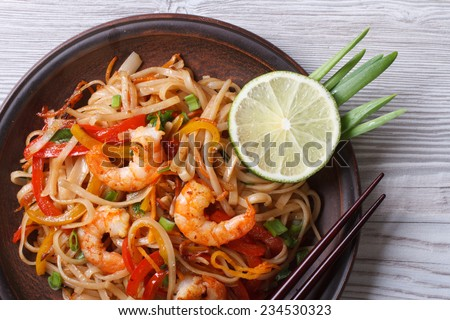 Asian rice noodles with shrimp and vegetables close-up on the table. top view of a horizontal  - stock photo