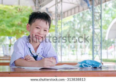 Asian schoolboy in uniform doing homework at school - stock photo