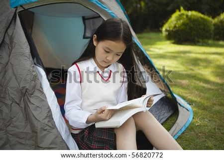 asian schoolgirl sitting in a tent and reading a book - stock photo