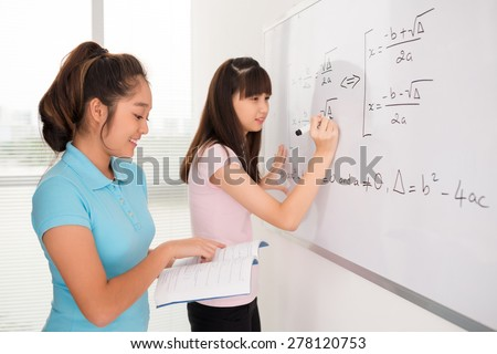 Asian schoolgirls writing equations from the manual of algebra on the whiteboard - stock photo