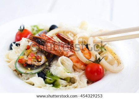 Asian seafood meal, chopsticks using for eating, closeup. Ingestion at chinese restaurant with traditional cutlery - stock photo