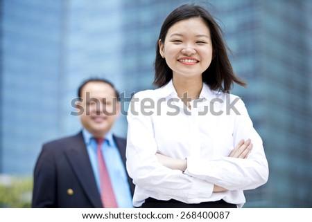 Asian senior businessman & young female executive portrait - stock photo