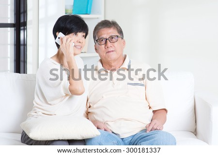 Asian senior couple calling on phone, using smartphone. Family living lifestyle at home. - stock photo