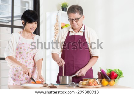 Asian senior couple preparing meal at kitchen. Seniors living lifestyle at home. - stock photo