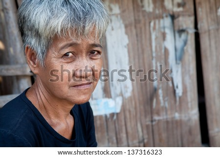 Asian senior from an impoverished area, outside her home in the Philippines - stock photo
