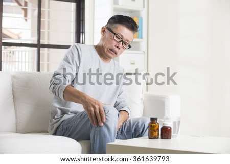 asian senior male with knees pain - stock photo
