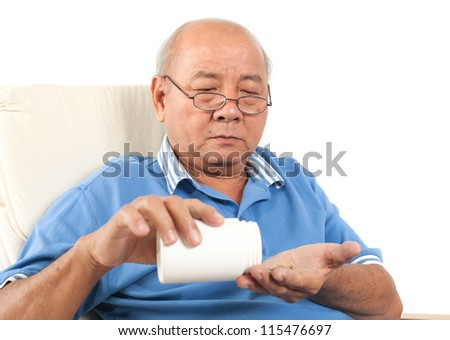 Asian senior man spilling pills onto hand. Isolated on white background. - stock photo