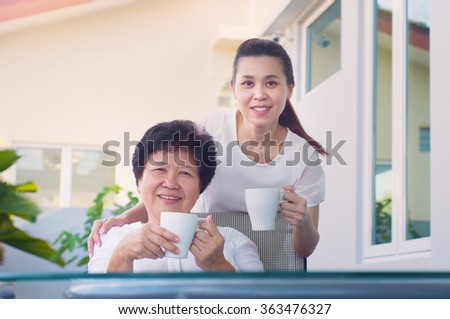 Asian senior woman and daughter relax in the garden - stock photo