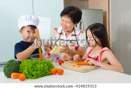 Asian senior woman and grandchildren prepared food in the kitchen - stock photo