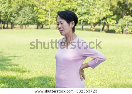 Asian senior woman back pain in the park  - stock photo