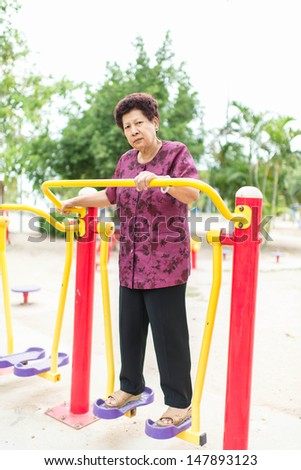 Asian senior woman exercising in the part outdoor - stock photo