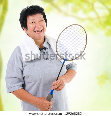 Asian senior woman healthy lifestyle. Happy Asian grandparent holding badminton racket - stock photo
