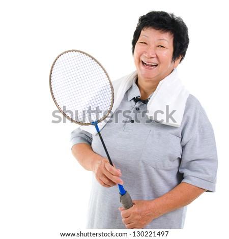 Asian senior woman healthy lifestyle. Happy Asian grandparent holding badminton racket isolated on white. - stock photo