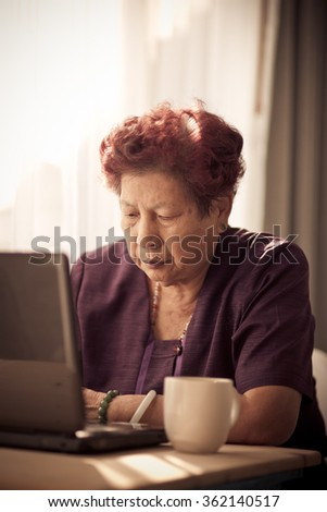Asian senior woman learning notebook at home.  Vintage tone. - stock photo