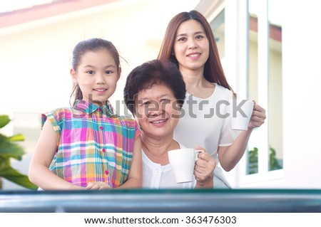 Asian senior woman relax in the garden together with daughter and grandchild - stock photo
