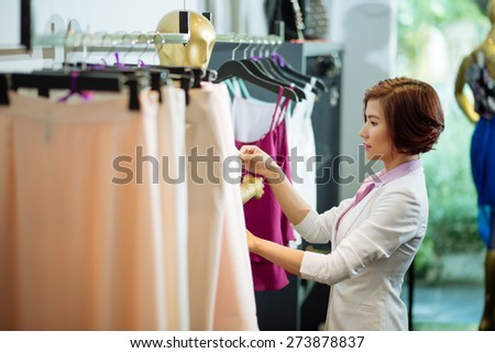 Asian shop manager dressing mannequin, side view - stock photo