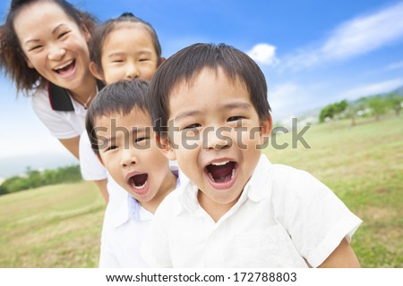 Asian smiling family playing on meadow and sunny day - stock photo