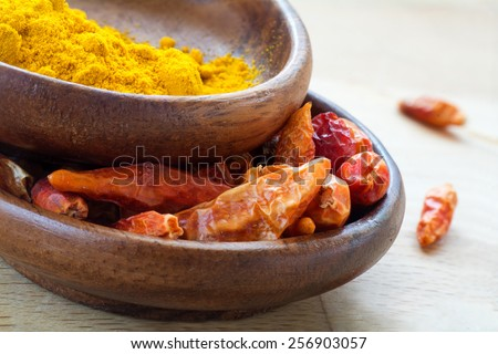 Asian spices, dried red chili and curcuma in wooden bowls, closeup - stock photo