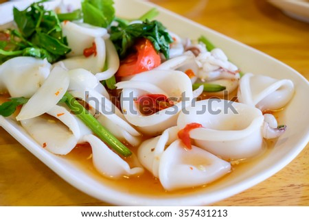 Asian spicy salad of squid with vegetables on a white plate - stock photo