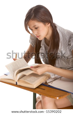 Asian student girl sitting by the desk and studying English dictionary in preparation for test, exam or spelling bee contest - stock photo