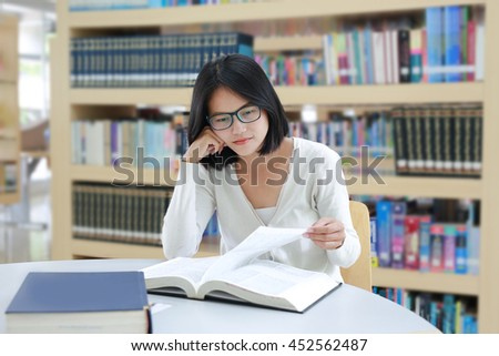 Asian student reading book in the library - stock photo
