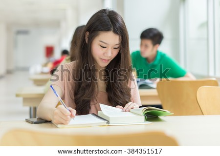 Asian student studying in the library - stock photo