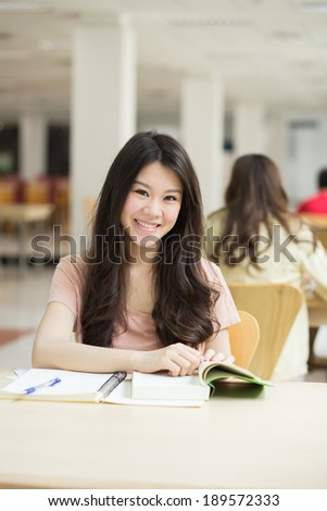 Asian student working in the library. - stock photo