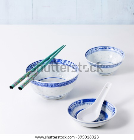 Asian style porcelain bowls and turquoise chopsticks over white kitchen table. Side view. Square image - stock photo