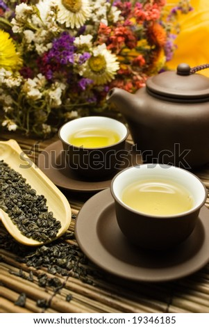 Asian tea set with dried green tea on a bamboo surface with a bunch of flowers in the background. - stock photo
