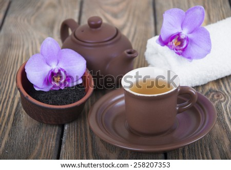 Asian tea set with orchid, black tea on a wooden background - stock photo