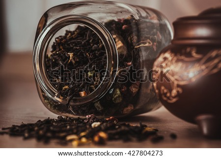 Asian teapot with dragon on stand and jar with scattering of fruit tea - stock photo