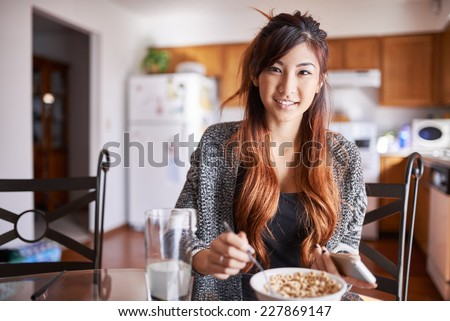 asian teen girl with smartphone in kitchen eating breakfast cereal - stock photo
