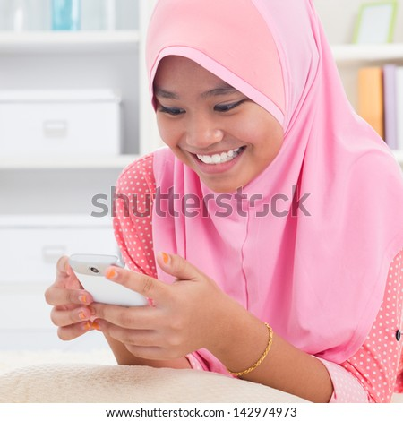 Asian teen texting on the phone. Southeast Asian teenager at home. Muslim teenage girl living lifestyle. - stock photo