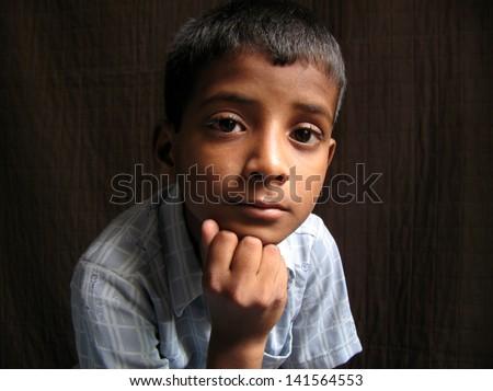 Asian teenage boy posing in the dark room - stock photo
