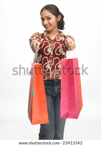 Asian teenage girl in modern costume carrying shopping  bags - stock photo