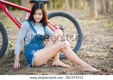 Asian teens girl standing with mountain bike in the park. - stock photo