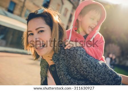 Asian Thai aunt plays with her 5 year old mixed race Asian Caucasian Australian nephew in the city. Filtered color shift, and sun flare effects. - stock photo