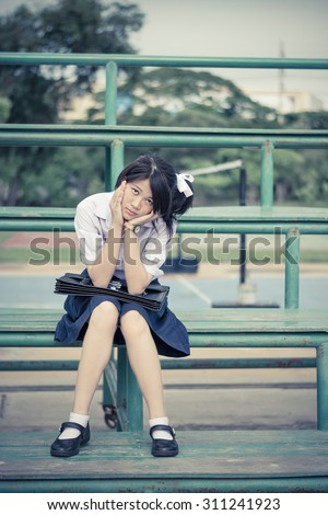 Asian Thai schoolgirl student in high school uniform education fashion is sitting on a metal stand and showing annoying facial expression in vintage retro color. She is not in good mood. - stock photo