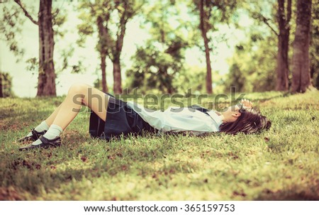 Asian Thai teenage female schoolgirl student in high school uniform with leather shoes lie down sleeping or relaxing on the grass field park with summer natural sunlight in old vintage retro - stock photo