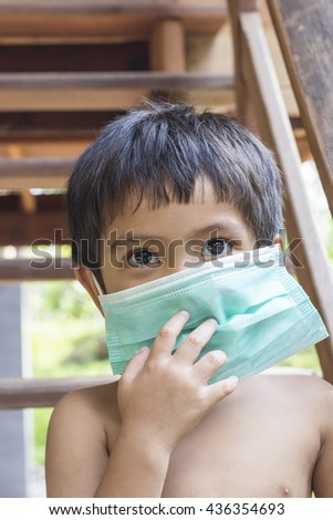 Asian Thai 4 years old boy wearing green medicine healthcare mask - stock photo