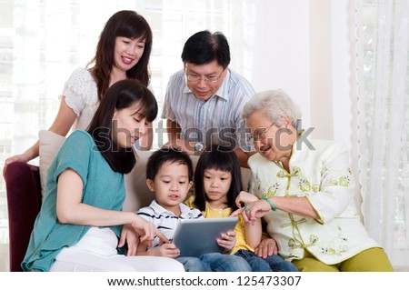 Asian three generations family having fun with tablet computer - stock photo